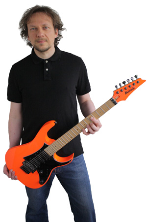 Marko Zirkovich holding an orange Ibanez electric guitar